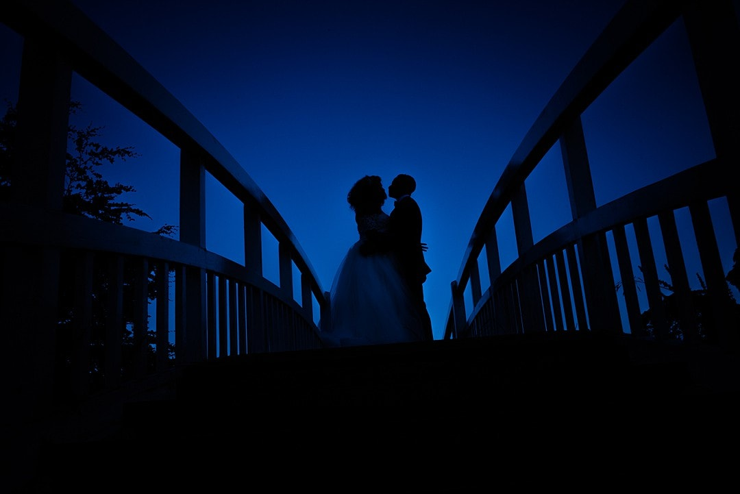 silhouette of the couple on the bridge at the fennes