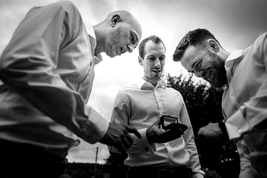 farbridge wedding photography groom and groomsmen looking at the wedding ring