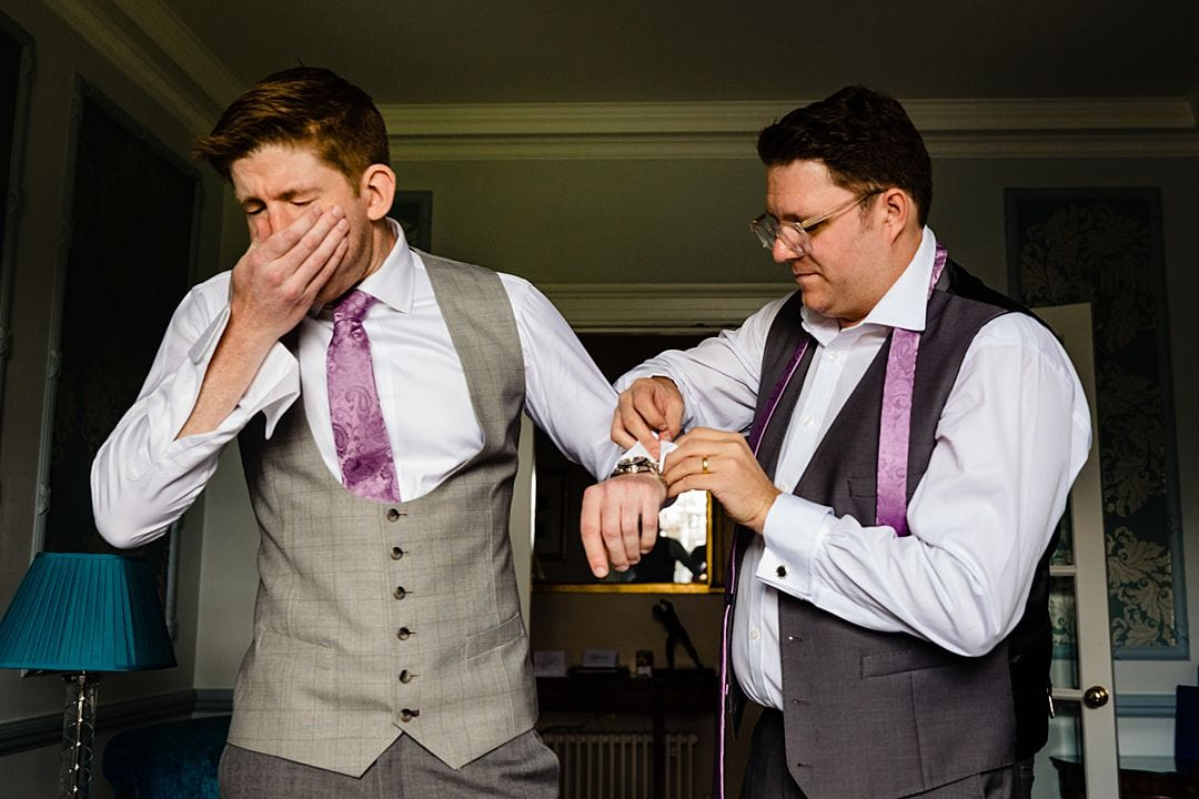 RAC Woodcote Park Wedding Photography groom getting ready about to sneeze