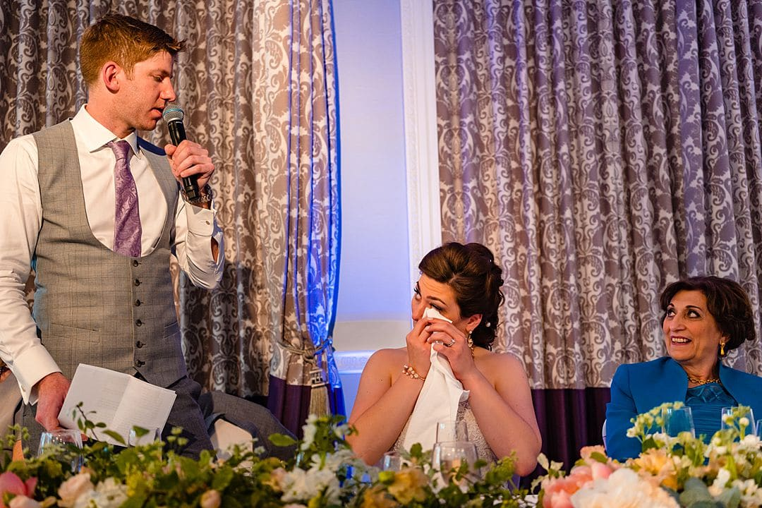 bride wiping tears during groom's speech at RAC Woodcote Park