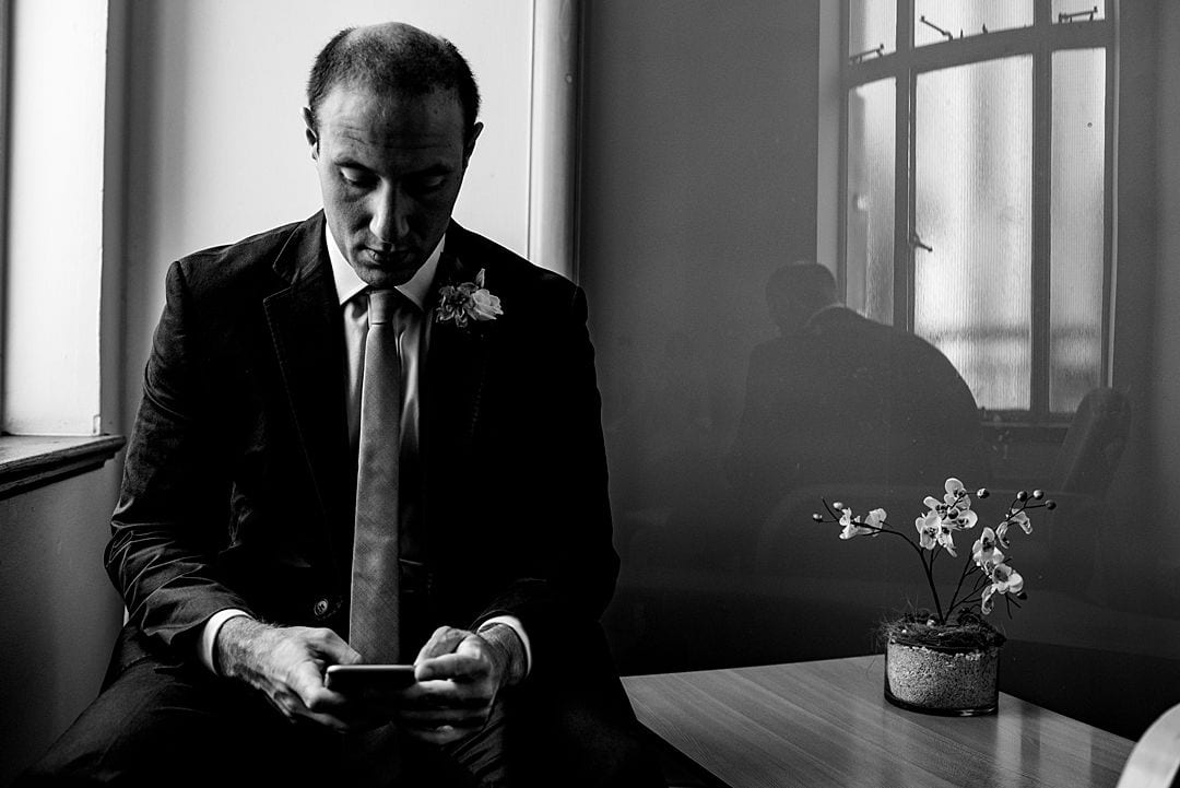 Wandsworth Town Hall Wedding Photography groom on mobile phone